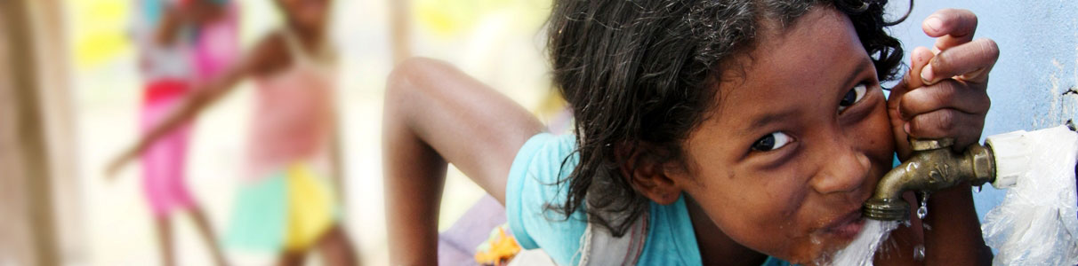A young girl in Nicaragua drinking safe, clean water from a WaterAid tap.